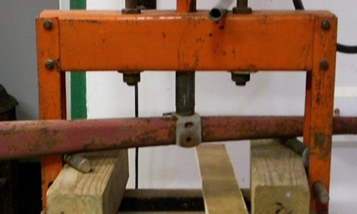 [Photo of radius rod in shop press]